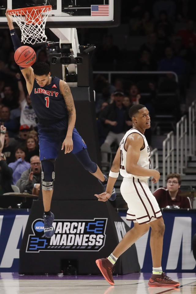 Liberty guard Caleb Homesley, left, dunks over Mississippi State guard Robert Woodard during the second half of a first-round game in the NCAA men's college basketball tournament Friday, March 22, 2019, in San Jose, Calif. (AP Photo/Jeff Chiu)