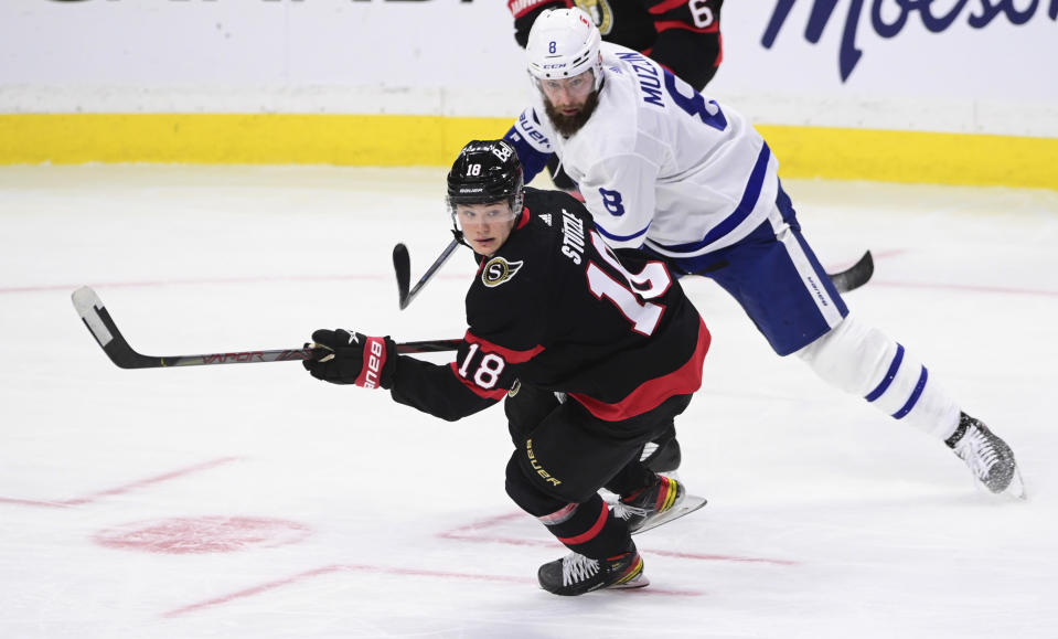 Ottawa Senators left wing Tim Stutzle (18) skates around Toronto Maple Leafs defenceman Jake Muzzin (8) during the second period of an NHL hockey game Friday, Jan. 15, 2021, in Ottawa, Ontario. (Sean Kilpatrick/The Canadian Press via AP)