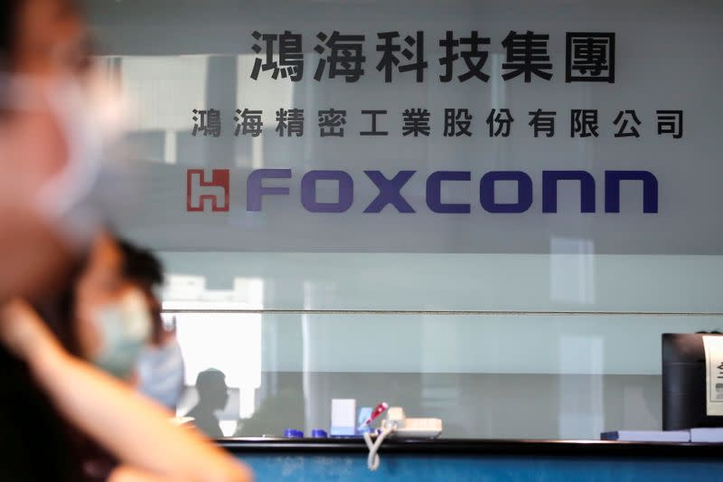 FILE PHOTO: People wear masks to protect themselves from coronavirus disease (COVID-19) while listening to the annual general meeting at the lobby of Foxconn's office in Taipei