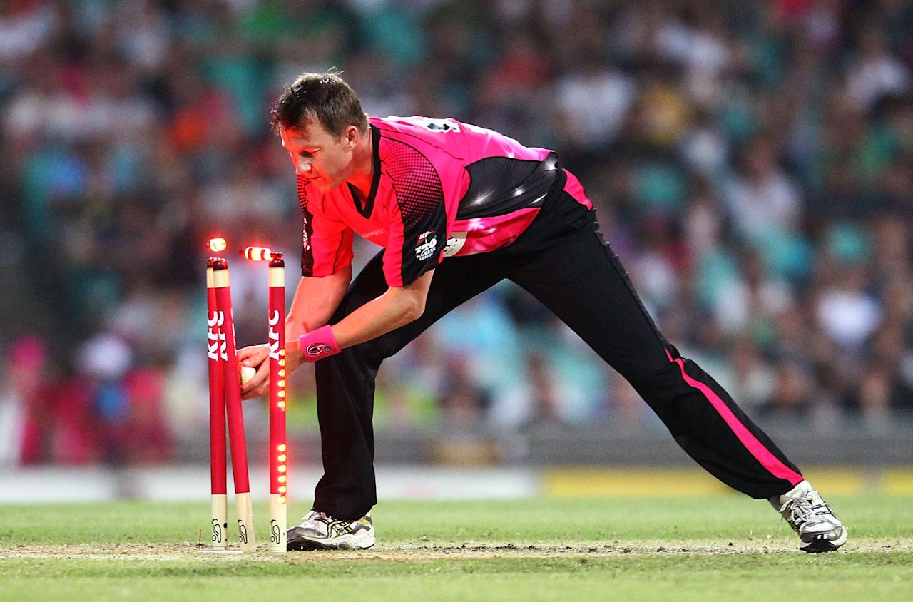 SYDNEY, AUSTRALIA - DECEMBER 08: Brett Lee attempts a run out during the Big Bash League match between the Sydney Sixers and the Sydney Thunder at Sydney Cricket Ground on December 8, 2012 in Sydney, Australia.  (Photo by Mark Nolan/Getty Images)