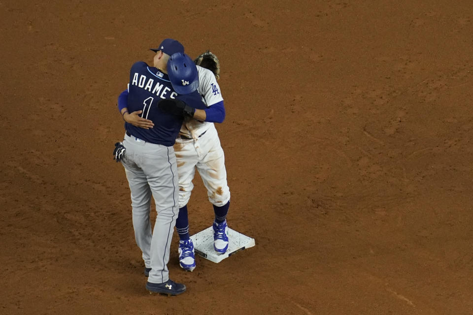 Los Angeles Dodgers' Mookie Betts gets a hug from Tampa Bay Rays shortstop Willy Adames after stealing second during the fifth inning in Game 1 of the baseball World Series Tuesday, Oct. 20, 2020, in Arlington, Texas. (AP Photo/David J. Phillip)
