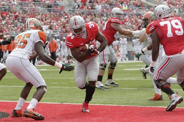 Ohio State running back Carlos Hyde, center, scores a touchdown in front of Florida A&M safety John Oye Ojo (25) during the first quarter of an NCAA college football game Saturday, Sept. 21, 2013, in Columbus, Ohio. (AP Photo/Jay LaPrete)