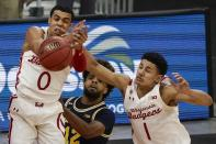Wisconsin's D'Mitrik Trice and Jonathan Davis go after a rebound against Michigan's Mike Smith during the second half of an NCAA college basketball game Sunday, Feb. 14, 2021, in Madison, Wis. (AP Photo/Morry Gash)