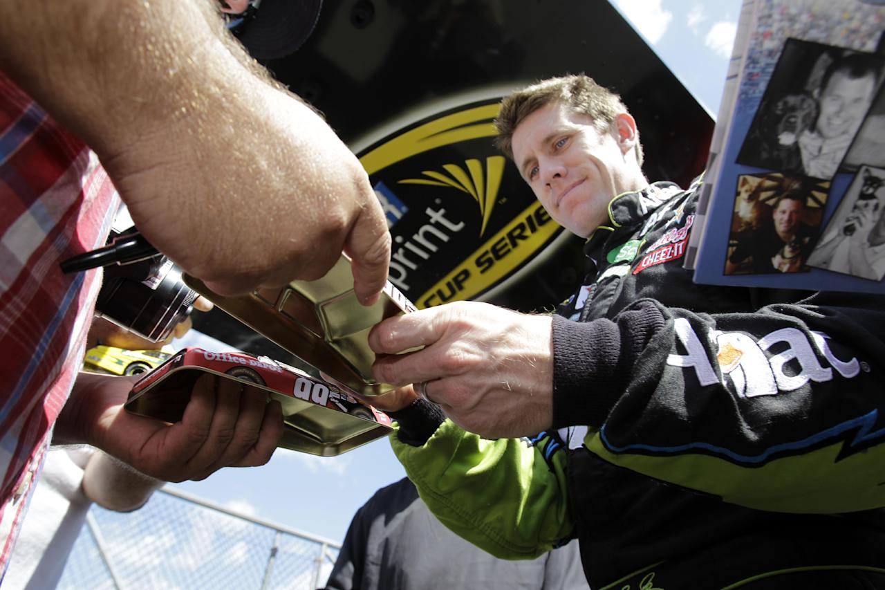 Carl Edwards signs autographs for fans before practice for the NASCAR Sprint Cup Series auto race at Watkins Glen International in Watkins Glen, N.Y., Friday, Aug. 12, 2011. (AP Photo/David Duprey)