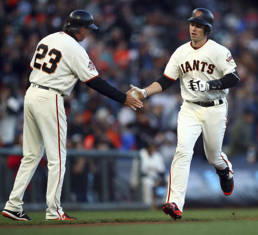 San Francisco Giants' Buster Posey, right, is congratulated by third base coach Ron Wotus (23) after hitting a home run off Miami Marlins pitcher Dan Straily during the first inning of a baseball game Tuesday, June 19, 2018, in San Francisco. (AP Photo/Ben Margot)