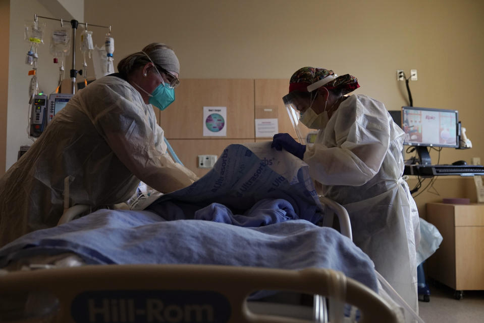 Registered nurses Robin Gooding, left, and Johanna Ortiz treat a COVID-19 patient at Providence Holy Cross Medical Center in the Mission Hills section of Los Angeles, Tuesday, Dec. 22, 2020. (AP Photo/Jae C. Hong)