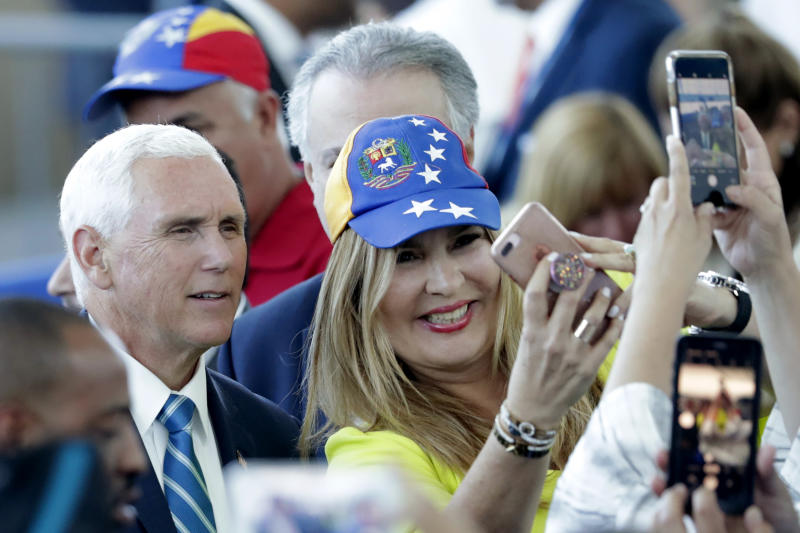 Vice President Mike Pence poses with Paula Tenreiro, who is wearing a cap with the design of the Venezuelan flag, following a tour on the USNS Comfort, Tuesday, June 18, 2019, in Miami. The hospital ship is scheduled to embark on a five-month medical assistance mission to Latin America and the Caribbean, including several countries struggling to absorb migrants from crisis-wracked Venezuela. (AP Photo/Lynne Sladky)