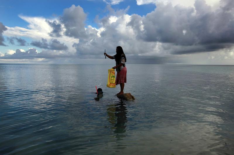 RNPS - PICTURES OF THE YEAR 2013 - Binata Pinata stands on top of a rock holding a fish her husband Kaibakia (L) has just caught off Bikeman islet, located off South Tarawa in the central Pacific island nation of Kiribati May 25, 2013. Kiribati consists of a chain of 33 atolls and islands that stand just metres above sea level, spread over a huge expanse of otherwise empty ocean. With surrounding sea levels rising, Kiribati's President Anote Tong has predicted his country will likely become uninhabitable in 30-60 years because of inundation and contamination of its freshwater supplies. REUTERS/David Gray (KIRIBATIE - Tags: ENVIRONMENT POLITICS SOCIETY ANIMALS TPX)