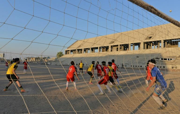 Football players train on the dusty pitch of the Al-Idara al-Mahalia stadium in Mosul which was once used by Islamic State group fighters as a weapons depot and a launchpad for rocket and mortar attacks