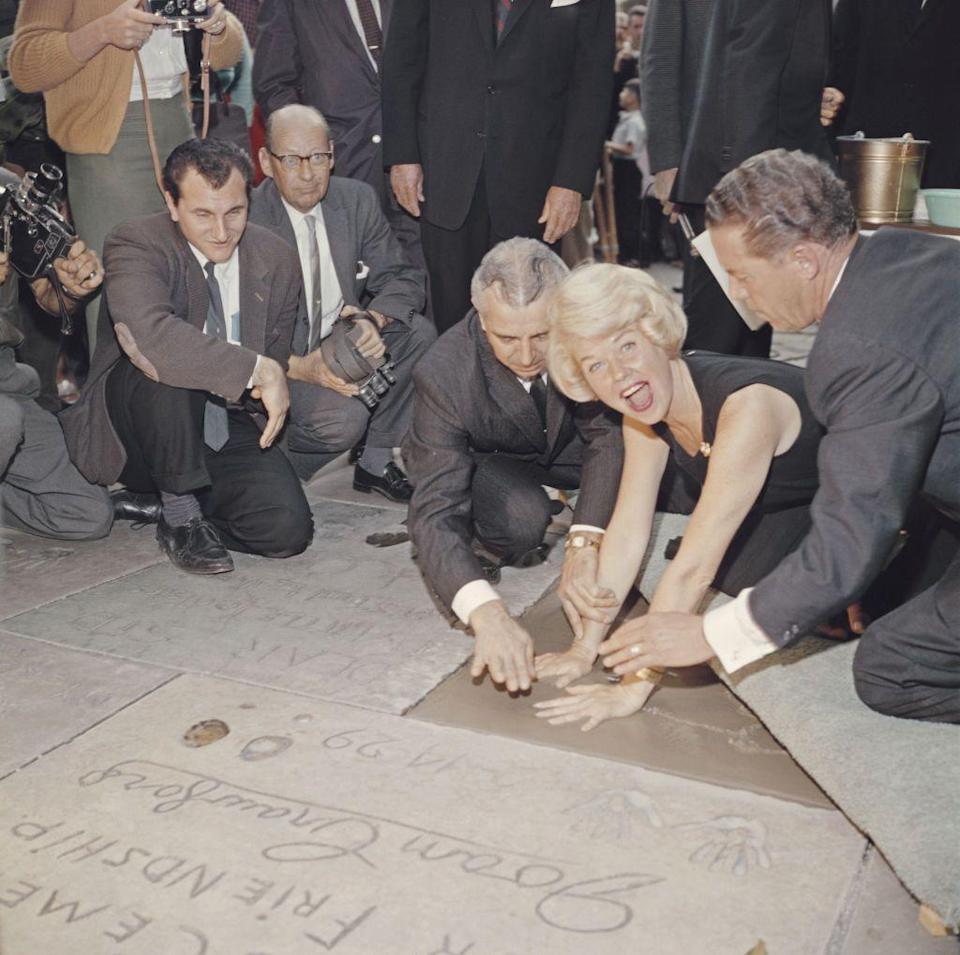 <p>Singer Doris Day leaves her handprints in cement at the entrance of Grauman's Chinese Theatre in Hollywood on January 19th, 1961.</p>
