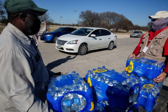 People collect water at a distribution site after winter weather caused electricity blackouts and water service disruption in Dallas