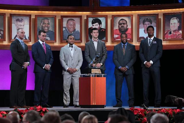 Heisman Trophy finalists, from left, Northern Illinois quarterback Jordan Lynch, Texas A&M quarterback Johnny Manziel, Auburn running back Tre Mason, Alabama quarterback AJ McCarron, Boston College running back Andre Williams and Florida State quarterback Jameis Winston stand behind the trophy before it was announced that Winston is this year's trophy winner at the Best Buy Theater, Saturday, Dec. 14, 2013 in New York. (AP Photo/Heisman Trust, Kelly Kline)