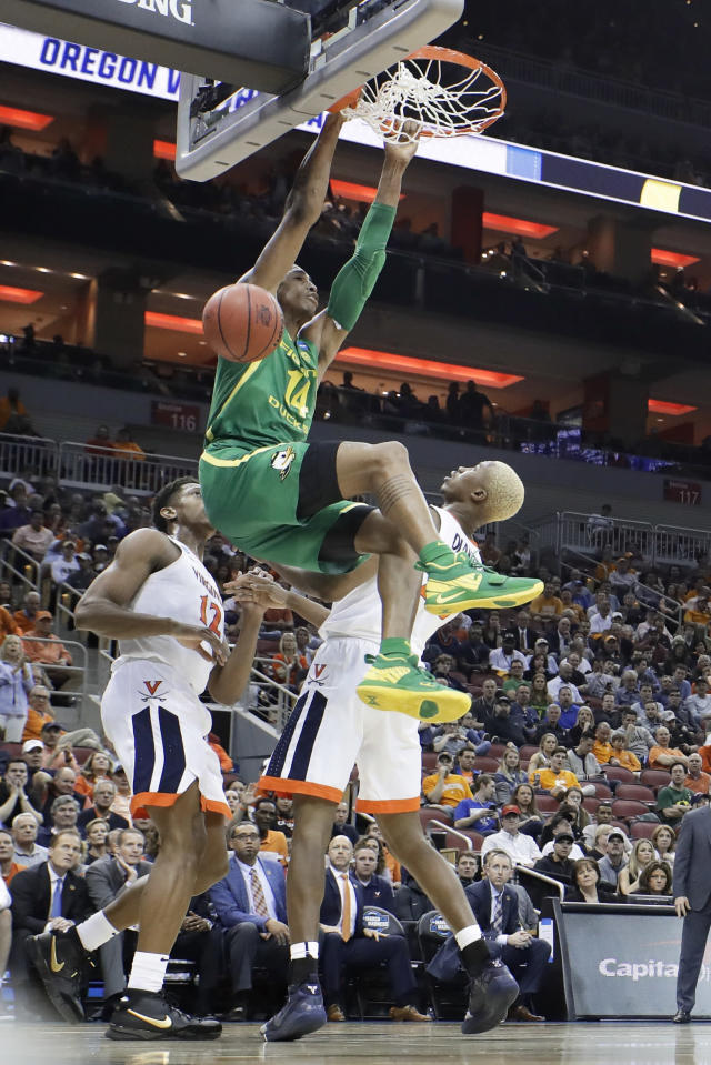 <p>Oregon's Kenny Wooten (14) dunks against Virginia's Mamadi Diakite, right, during the first half of a men's NCAA Tournament college basketball South Regional semifinal game, Thursday, March 28, 2019, in Louisville, Ky. (AP Photo/Timothy D. Easley) </p>