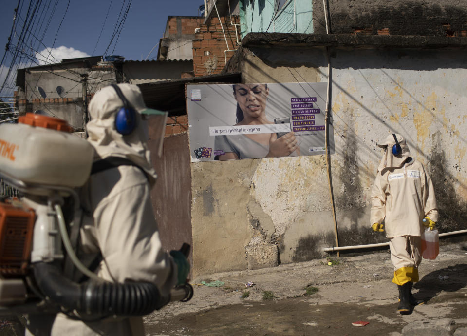 Water utility workers from CEDAE disinfect the Mare Complex slum in an effort to curb the spread of the new coronavirus, in Rio de Janeiro, Brazil, Monday, May 4, 2020. (AP Photo/Silvia Izquierdo)