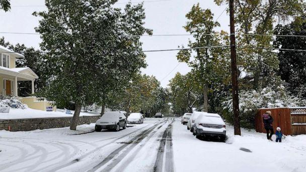 PHOTO: Pedestrians make their way along a snow covered street lined with trees that still have their leaves during a fall snowstorm in Helena, Mont., Sept. 29, 2019. (Matt Volz/AP)