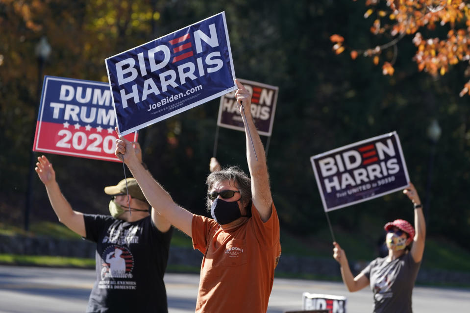 Supporters of President-elect Joe Biden wave signs at the entrance to Trump National golf club in Sterling, Va., Saturday Nov 7, 2020. Trump was at the facility. (AP Photo/Steve Helber)