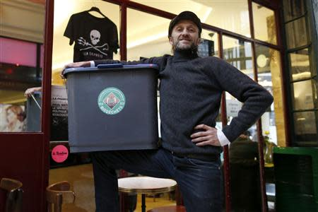 Stephan Martinez, owner of Le Petit Choiseuil bistrot, poses with a garbage container to collect food waste in Paris