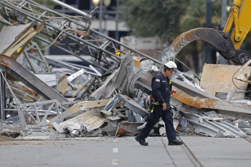 FILE - In this Wednesday, Oct. 16, 2019 file photo, A worker walks in front of rubble in the street at the site of the Hard Rock Hotel in New Orleans. Dozens of protesters marched from the site of the partially collapsed Hard Rock Hotel on the edge of the French Quarter to City Hall on Friday, Jan. 24, 2020 demanding that something be done about the hotel and that the two bodies still inside be recovered.  (AP Photo/Gerald Herbert, File)