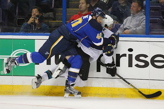 ST. LOUIS, MO - OCTOBER 15: Maxim Lapierre #40 of the St. Louis Blues checks Dan Boyle #22 of the San Jose Sharks into the boards at the Scottrade Center on October 15, 2013 in St. Louis, Missouri. Boyle was injured on the play and had to leave the ice on a stretcher. (Photo by Dilip Vishwanat/Getty Images)