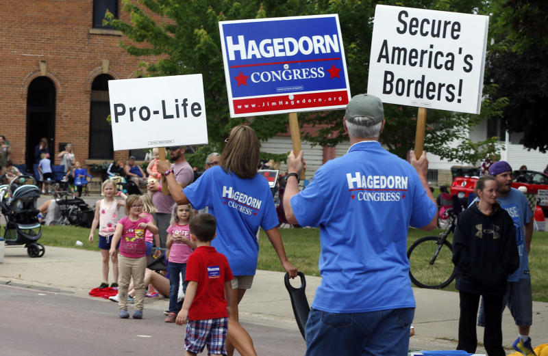 In this June 10, 2018 photo, volunteers for Minnesota 1st District congressional candidate Jim Hagedorn carry signs during a parade in Waterville, Minn. Waterville's 54th annual Bullhead Days parade included Republican Hagedorn and Democrat Dan Feehan, candidates who came to shake as many hands as they could in the open seat race which promises to be one of the most closely watched races in the country. (AP Photo/Jim Mone)