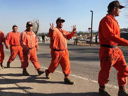 Prison inmates head out to the day's work of battling the blazes at fire command center in Santa Rosa, California, U.S October 14, 2017. REUTERS/Heather Somerville.