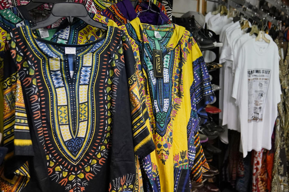 Colorful Dashiki garments are displayed for sale at Billie Parker's Black Wall Street Market, Saturday, April 10, 2021, in Tulsa, Okla. Her establishment, in an underdeveloped and underserved section of the city, is a far cry from the booming city within a city that was Greenwood, with its Black grocers, shopkeepers, doctors, lawyers, newspaper publishers and other businessmen and women. But Parker thought it was important to lay claim to the name and its legacy. (AP Photo/Sue Ogrocki)