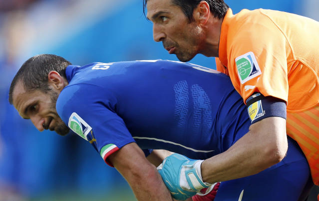 Italy's goalkeeper Gianluigi Buffon, right, holds on to Italy's Giorgio Chiellini during the group D World Cup soccer match between Italy and Costa Rica at the Arena Pernambuco in Recife, Brazil, Friday, June 20, 2014. (AP Photo/Frank Augstein)