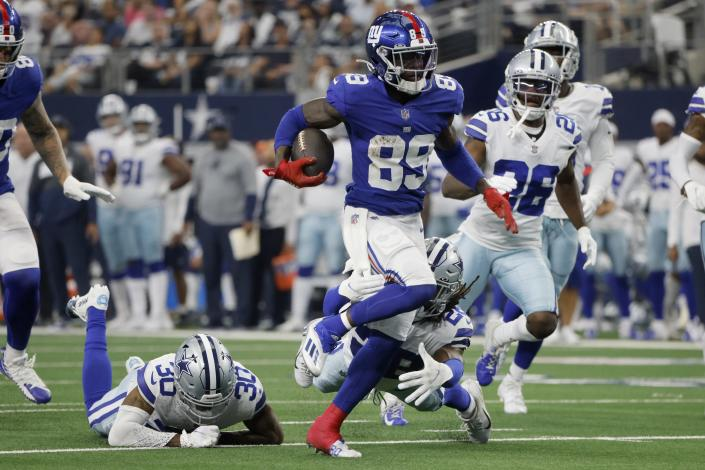 New York Giants wide receiver Kadarius Toney (89) escapes tackle attempts by Dallas Cowboys' Anthony Brown (30) and safety Malik Hooker, bottom right, as Toney gains long yardage after a catch in the first half of an NFL football game in Arlington, Texas, Sunday, Oct. 10, 2021. (AP Photo/Michael Ainsworth)