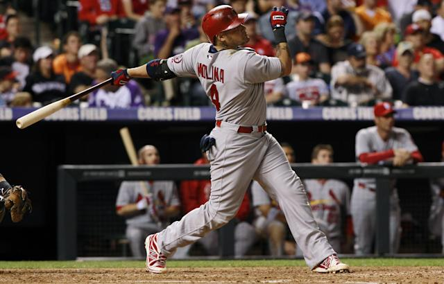 St. Louis Cardinals' Yadier Molina follows the flight of his RBI-single against the Colorado Rockies in the fifth inning of the Cardinals' 4-3 victory in a baseball game in Denver on Wednesday, Sept. 18, 2013. (AP Photo/David Zalubowski)