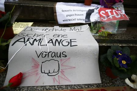Flowers and posters are placed in the square between the city cathedral and the railway station in Cologne, Germany, January 11, 2016, where the vast majority of dozens of New Year Eve assaults on women took place. The texts read 'Sexual harassement against women will be NOT tolerated' and 'Next time for sure an arm length in advance'. REUTERS/Wolfgang Rattay