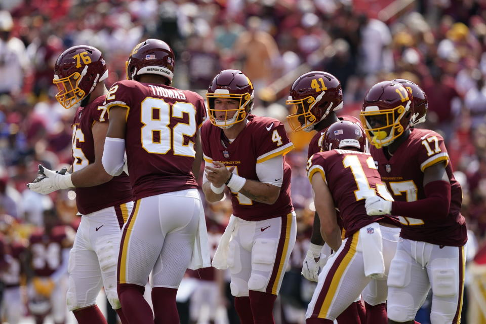 Washington Football Team quarterback Taylor Heinicke (4) in the huddle with teammates during the first half of an NFL football game against the Los Angeles Chargers, Sunday, Sept. 12, 2021, in Landover, Md. (AP Photo/Alex Brandon)