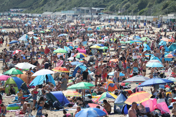 People gather on Bournemouth Beach, following the relaxation of the coronavirus lockdown restrictions in the country, in Bournemouth, England, Tuesday June 2, 2020. (Andrew Matthews/PA via AP)