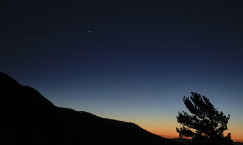 "In this photograph taken from Shenandoah National Park in Luray, Virginia, you can see the planets Saturn and Jupiter nestled close together in the sky at sunset. Saturn and Jupiter are nearing a ""great conjunction"" on Dec. 21. During the exciting, astronomical event, the two planets will appear to be so close together in the sky, they will be just a tenth of a degree apart from one another."