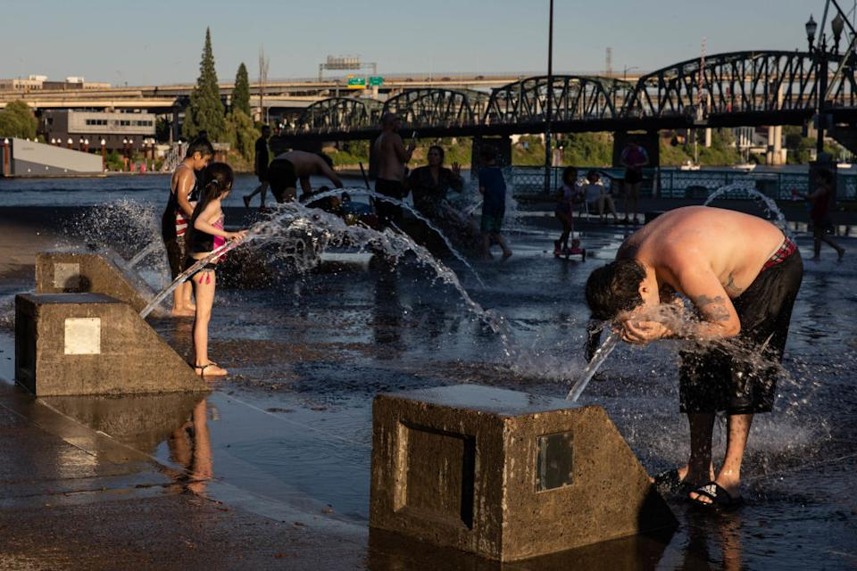 A boy cools off in a water fountain as other children stand nearby on the riverside during a heatwave in Portland.