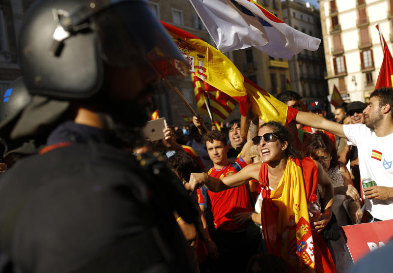 Demonstrators challenge Catalan Mossos d'Esquadra regional police officers at the end of a march in downtown Barcelona, Spain, to protest the Catalan government's push for secession from the rest of Spain, Sunday Oct. 8, 2017. Sunday's rally comes a week after separatist leaders of the Catalan government held a referendum on secession that Spain's top court had suspended and the Spanish government said was illegal. (AP Photo/Francisco Seco)