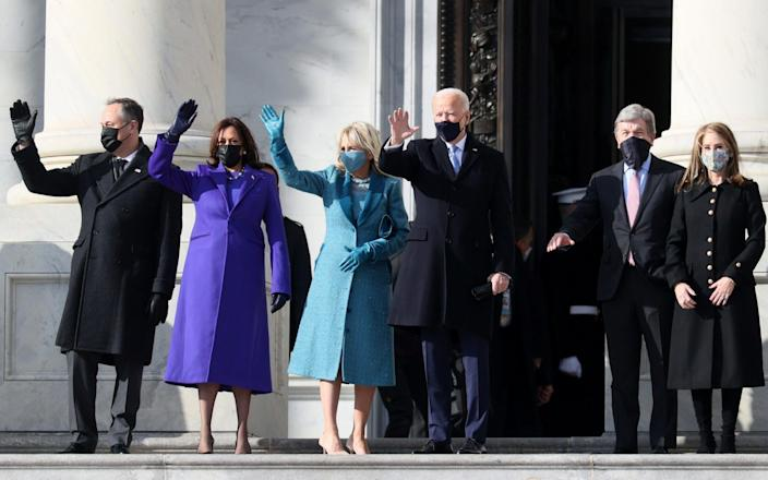 (L-R) Doug Emhoff, U.S. Vice President-elect Kamala Harris, Jill Biden and President-elect Joe Biden wave as they arrive on the East Front of the U.S. Capitol for the inauguration - Joe Raedle/Getty Images North America