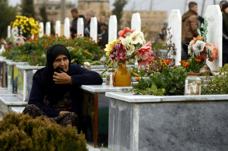 A woman in the northeastern Syrian town of Qamishli visits a grave during the funeral of a fighter from the Kurdish-led YPJ. The Syrian Kurdish administration is seeking an international tribunal to try members of the Islamic State group