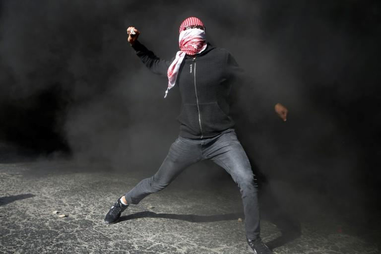 A Palestinian protestor throws stones towards Israeli forces in the West Bank city of Ramallah on December 11, 2017 as protests continue in the Middle East and elsewhere over US President Donald Trump's declaration of Jerusalem as Israel's capital