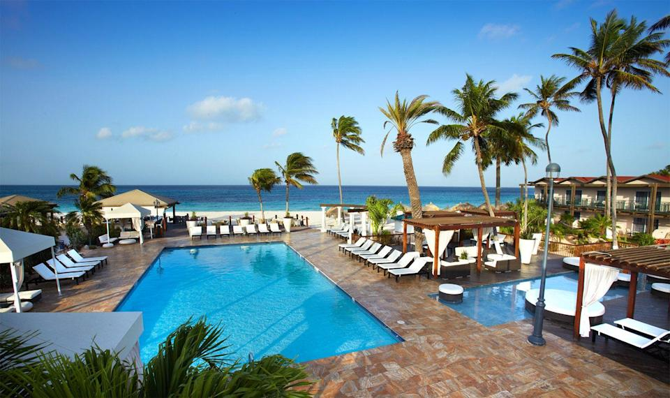 """<p><strong><a href=""""https://www.tamarijnaruba.com/"""" rel=""""nofollow noopener"""" target=""""_blank"""" data-ylk=""""slk:Tamarijn Aruba, Oranjestad, Aruba"""" class=""""link rapid-noclick-resp"""">Tamarijn Aruba, Oranjestad, Aruba</a></strong><br>This Caribbean resort pulls out all the stops for couples who've just made it official. With a marriage certificate or an invitation as proof, you'll be able to enjoy a number of exclusive perks, including an upgrade to an oceanfront villa, free dance lessons, and a complimentary bottle of Champagne. To make sure you'll come back for more, a gift certificate for a free night on your first anniversary is also available.</p><span class=""""copyright"""">Photo: Courtesy of Tamarijn.</span>"""