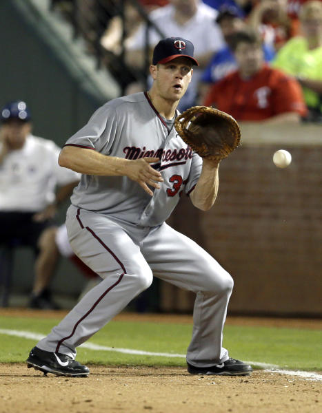 FILE - In this Aug. 30, 2013, file photo, Minnesota Twins first baseman Justin Morneau fields a ground out by Texas Rangers' A.J. Pierzynski in the eighth inning of a baseball game in Arlington, Texas. The Twins have traded Morneau to the Pittsburgh Pirates on Saturday, Aug. 31, 2013,, sending the veteran first baseman to a playoff-contending team for the final month of the season, (AP Photo/Tony Gutierrez, File)
