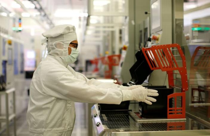 FILE PHOTO: Bosch employee holds semiconductor wafer in clean room in company manufacturing base in Reutlingen