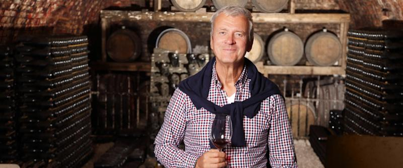 Portrait of senior standing at wine cellar while holding in his hand a glass of red wine and looking at camera