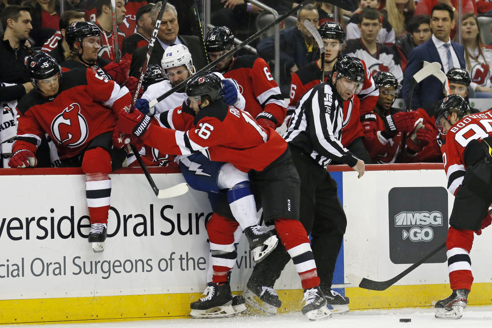 New Jersey Devils center Kevin Rooney (16) checks Tampa Bay Lightning right wing Nikita Kucherov (86) into the Devils' bench during the first period of an NHL hockey game Sunday, Jan. 12, 2020, in Newark, N.J. (AP Photo/Adam Hunger)