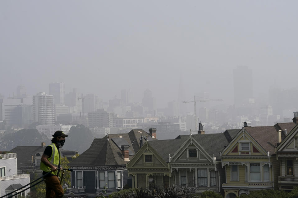 "A worker cleans grass at Alamo Square Park as smoke from wildfires and fog obscures the skyline above the ""Painted Ladies,"" a row of historical Victorian homes, in San Francisco, Monday, Sept. 14, 2020. (AP Photo/Jeff Chiu)"
