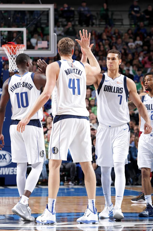 DALLAS, TX - MARCH 16: Dirk Nowitzki #41 and Dwight Powell #7 of the Dallas Mavericks high five during the game against the Cleveland Cavaliers on March 16, 2019 at the American Airlines Center in Dallas, Texas. (Photo by Glenn James/NBAE via Getty Images)