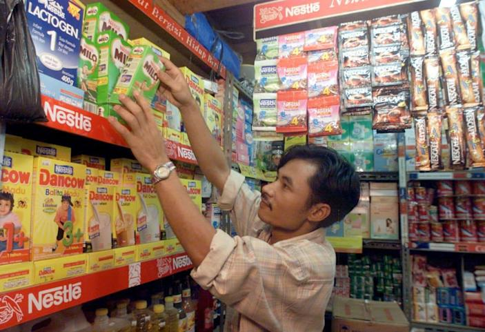 """<div class=""""inline-image__caption""""> <p>An Indonesian shopkeeper stocks the shelves of his market stall with Nestlé products in Jakarta.</p> </div> <div class=""""inline-image__credit""""> Reuters </div>"""