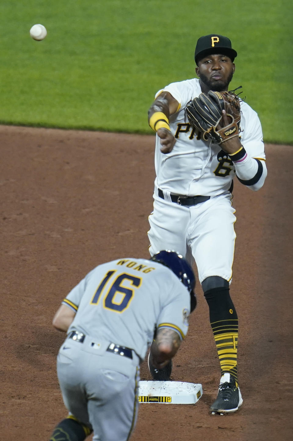 Pittsburgh Pirates second baseman Rodolfo Castro relays the ball to first after Milwaukee Brewers' Kolten Wong was forced out on the front end of a double play hit into by Willy Adames during the eighth inning of a baseball game Tuesday, July 27, 2021, in Pittsburgh. (AP Photo/Keith Srakocic)