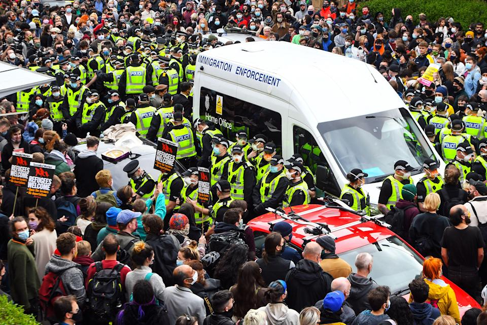 <p>Protesters surround an Immigration Enforcement van to stop it from departing after individuals were detained in Glasgow on 13 May 2021</p> (AFP via Getty Images)