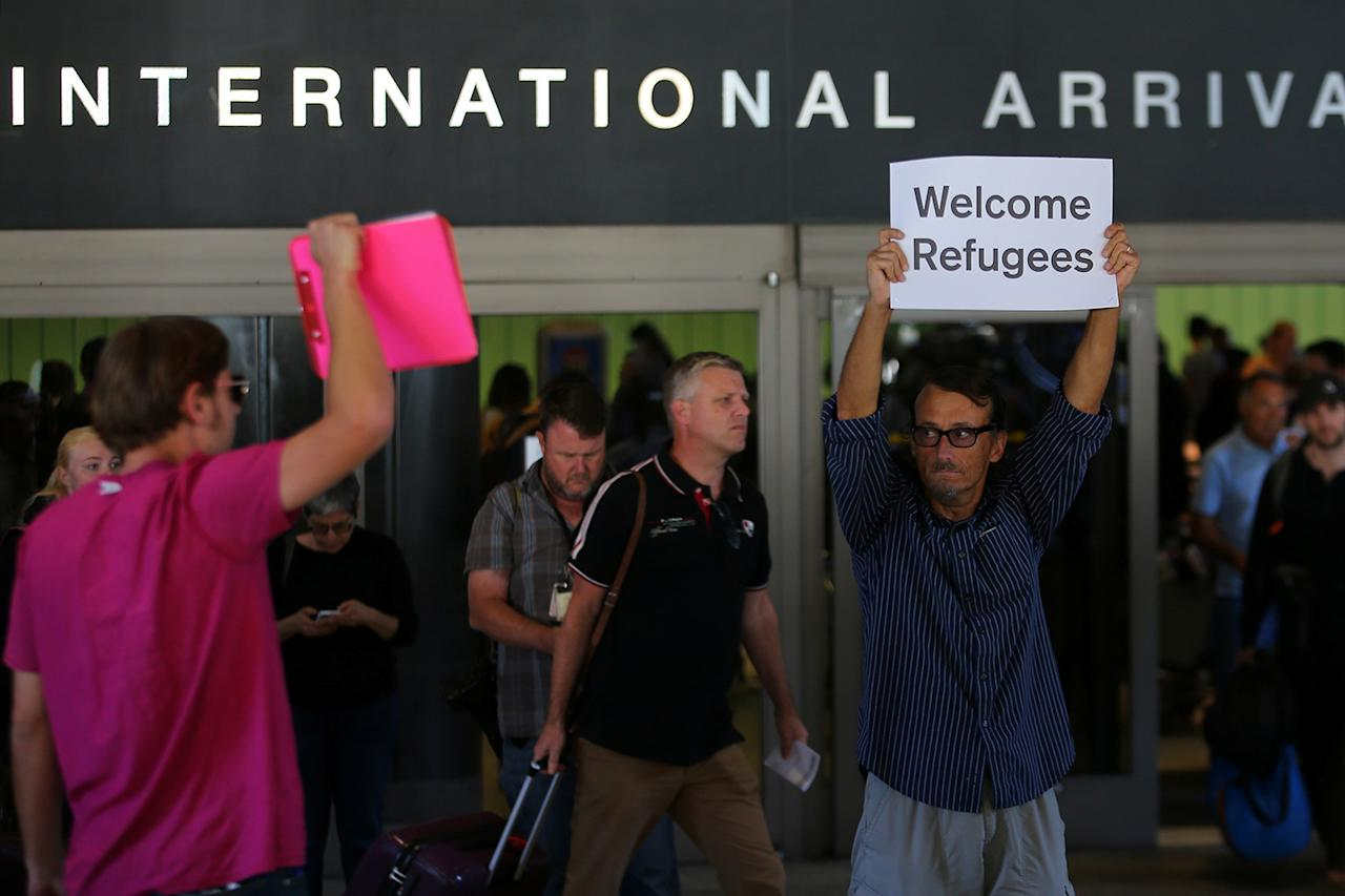 "<p>Retired engineer John Wider, 59, is greeted by a supporter of U.S. President Donald Trump as he holds up a sign reading ""Welcome Refugees"" at the international arrivals terminal at Los Angeles International Airport in Los Angeles, California, U.S., June 29, 2017. (Mike Blake/Reuters) </p>"