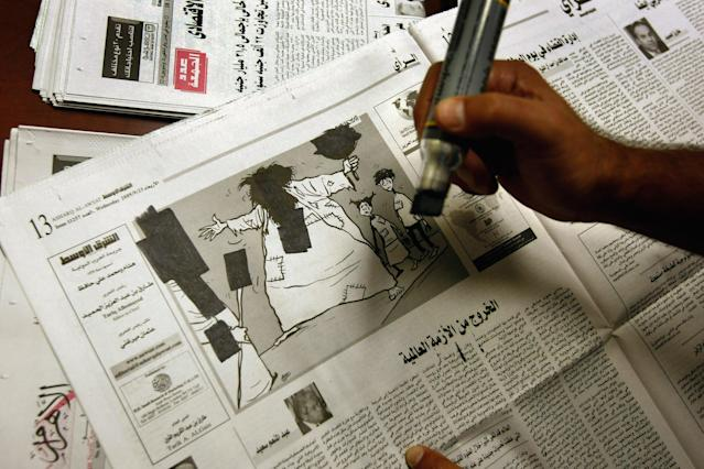 """GUANTANAMO BAY, CUBA - OCTOBER 27: (EDITORS NOTE: Image has been reviewed by U.S. Military prior to transmission.) An Arabic translator censors out selected images and news articles from a newspapers before detainees are permitted to read them inside the U.S. military prison for """"enemy combatants"""" on October 27, 2009 in Guantanamo Bay, Cuba. Although U.S. President Barack Obama pledged in his first executive order last January to close the infamous prison within a year's time, the government has been struggling to try the accused terrorists and to transfer them out ahead of the deadline. Military officials at the prison point to improved living standards and state of the art medical treatment available to detainees, but the facility's international reputation remains tied to the """"enhanced interrogation techniques"""" such as waterboarding employed under the Bush administration. (Photo by John Moore/Getty Images)"""